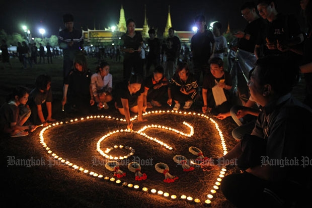 Mourners arrange candles to create a heart encasing the number nine, marking the reign of the late King, at Sanam Luang. (Photo by Wichan Charoenkiatpakul)