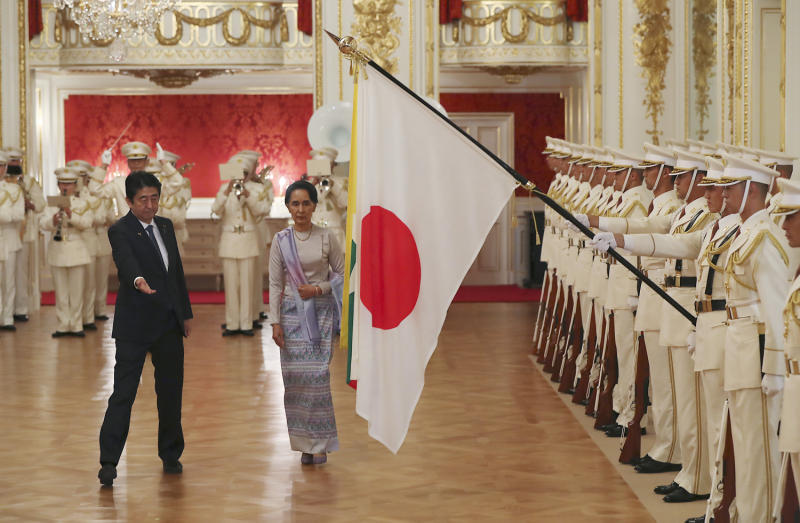 Myanmar de facto leader Aung San Suu Kyi, accompanied by Japan's Prime Minister Shinzo Abe, reviews a guard of honour before their meeting at the Akasaka Palace state guest house in Tokyo on Wednesday. (AFP photo)
