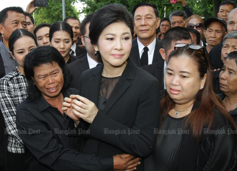 A farmer from Ubon Ratchathani (left) hugs Yingluck Shinawatra to show her support while the former prime minister arrives at the Supreme Court to defend the rice-pledging scheme.