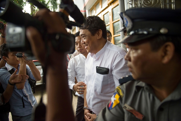 Than Htut Aung, CEO of the Eleven Media Group, is escorted by police from the court in Yangon on Friday. He and his chief editor will spend the next two weeks in Insein prison while defamation allegations against them are investigated. (AFP Photo)
