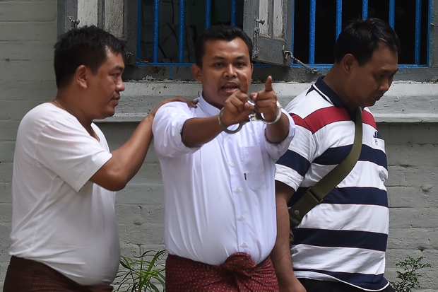 Police escort a handcuffed Wai Phyo, chief editor of Eleven Media Group, following his court appearance in Yangon on Friday. (AFP Photo)