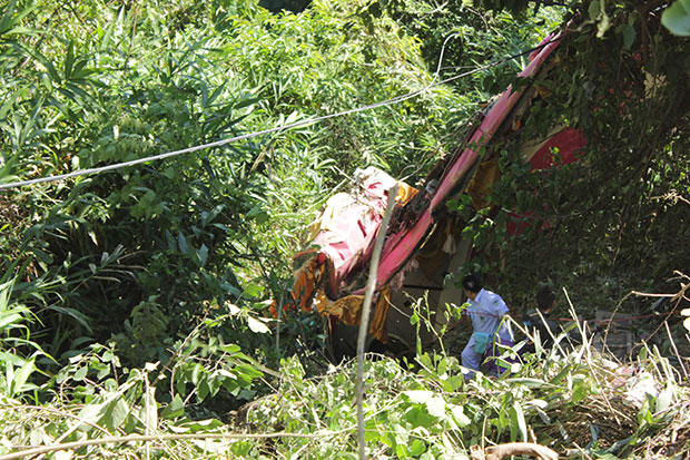 The wreckage of the tour bus in the ravine after it plunged off a winding hill road in Uttaradit's Muang district, killing 18 people and injuring 20 others, on Tuesday morning. The victims were retired employees of state-run CAT Telecom Plc on a holiday. (Photo by Boonnam Kerdkaew)