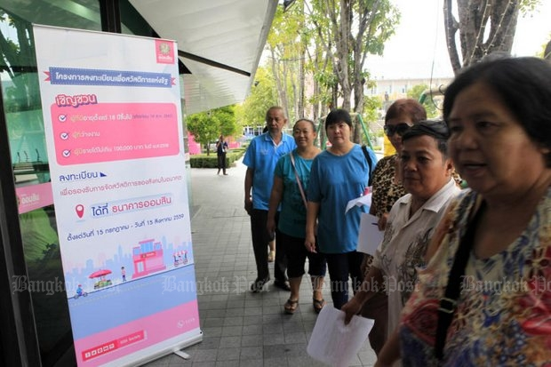 The government sponsored a sign-up last July at the Government Savings Bank for the populist welfare programme for the poor. (Photo by Apichit Jinakul)