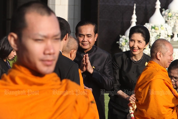 Prime Minister Prayut Chan-o-cha and his wife give alms to monks at Government House on Thursday morning. (Photo by Thiti Wannamontha)