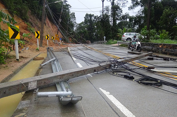 Electricity poles brought down by fallen rocks block a road on Koh Phangan in Surat Thani on Monday. (Photo by Supapong Chaolan)