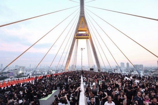 An estimated 50,000 subjects converged Monday on the Bhumibol 1 Bridge to make merit to 999 Buddhist monks and observe 89 seconds of silence in honour of the 89th birth anniversary of KingBhumibol Adulyadej. (Photos by Wichan Charoenkiatpakul)