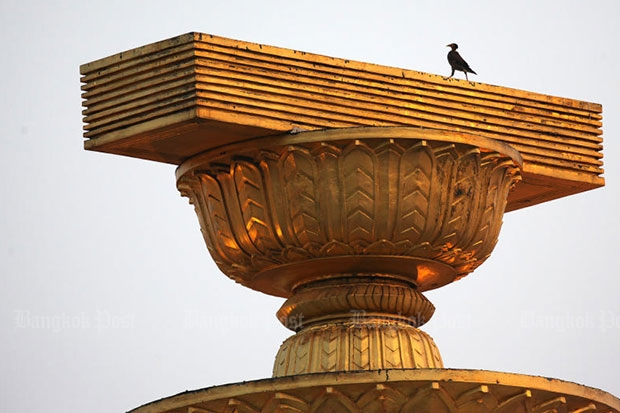 A bird stands on a replica constitution at the top of Democracy Monument on Ratchadamnoen Klang Avenue in Bangkok. (Bangkok Post file photo)
