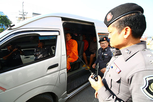 A police officer stops a van carrying a monk and disciples of Wat Phra Dhammakaya for a search at a checkpoint in Pathum Thani. (Photo by Pongpat Wongyala)