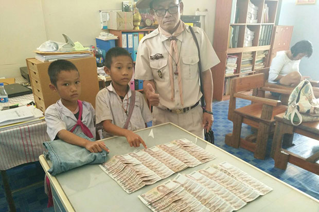Two schoolboys, Khamnon Kaengwichit, 9, and his cousin Nawapon Sopasaereesuk, 9, both Prathom 1 students at Ban Khun Huay Mae Thor School in Tak's Mae Ramat district, with the money they found in the donated jeans, also on the table. (Photo by Assawin Pinitwong)
