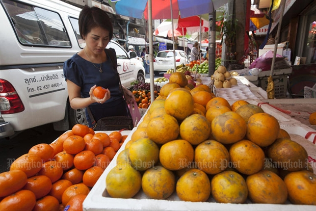 A woman examines citrus fruit for sale at a market in Charoen Krung road in February 2016. (Bangkok Post file photo)