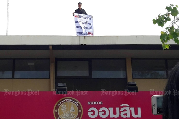 Chalerm Sonnonthee climbed a roof near Government House, threw giant firecrackers to get attention, and waved a banner demanding that the prime minister help him find justice. (Photo by Thanarak Khunton)