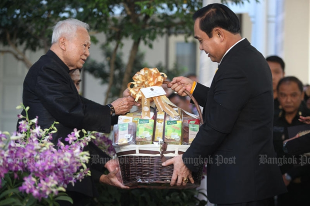 Prime Minister Prayut Chan-o-cha presents Privy Council president Prem Tinsulanonda with a gift basket as cabinet members and armed forces chiefs give him their New Yearf blessings on Thursday morning.(Photo by Thiti Wannamontha)