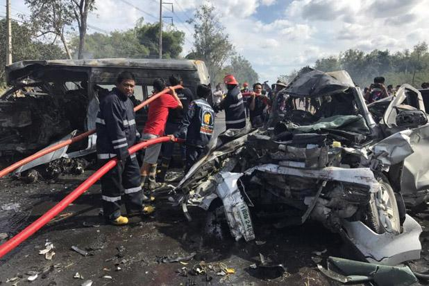 Emergency service crews finish extinguishing the fire that killed 25 people after a passenger van swerved and crashed into a pickup truck in Ban Bung district, Chon Buri, on Monday. (Photo by Sawang Rescue foundation.)