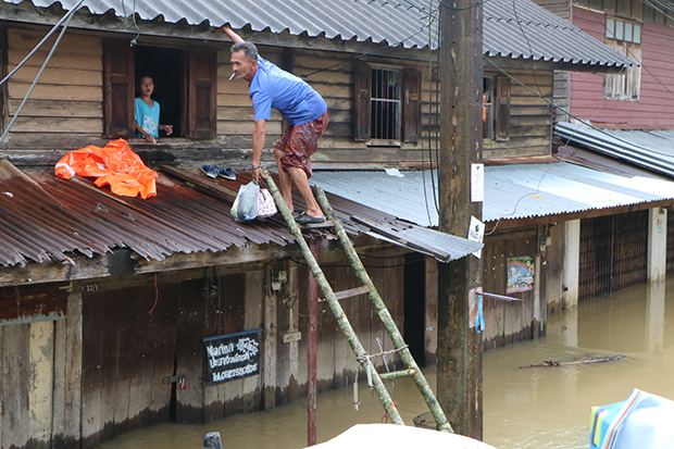 A man climbs on a bamboo ladder to enter his flooded house through a second-floor window in Narathiwat on Thursday. (Photo by Waedao Harai)