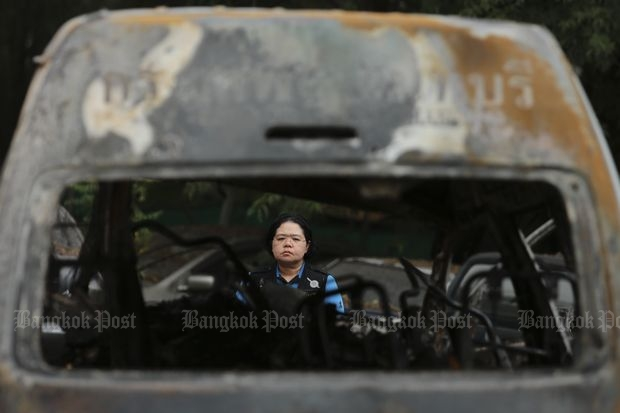 A Chon Buri forensic official on Thursday inspects the charred wreckage of the van involved in a crash which killed 25 in the eastern province on Monday. (Photo by Patipat Janthong)