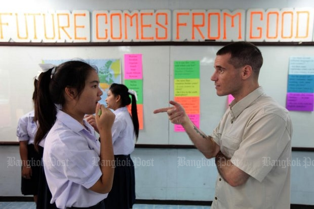 A student at Kunnatee Ruttharam Wittayakom School, left, practises speaking English with her teacher, Guillaume Langlois, who is French. (File photo by Jetjaras na Ranong)