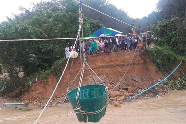 This pulley line with a basket to carry people and supplies was erected across a   flooded canal after the bridge was washed away in Nop Phi Tam district of Nakhon Si Thammarat on Thursday afternoon. (Photo by Nujaree Raekrun)