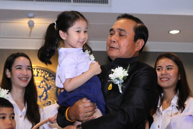 Prime Minister Prayut Chan-o-cha hoisted and chatted with children at Government House Tuesday, ahead of Saturday's National Children's Day. (Pool photo)