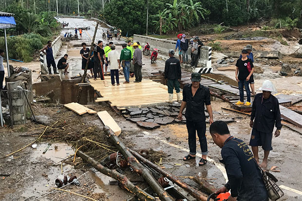 Residents repair the flood-damaged bridge on the main entry road to their village in Bang Saphan district, Prachuap Khiri Khan on Thursday. (Photo by Chaiwat Satyaem)