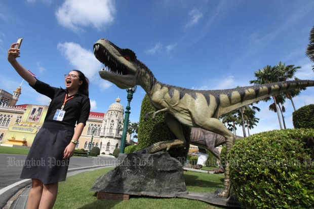 An official at Government House takes a selfie in front of a dinosaur model installed at Government House on Thursday for Children's Day activities this Saturday. (Photo by Thiti Wannamontha)