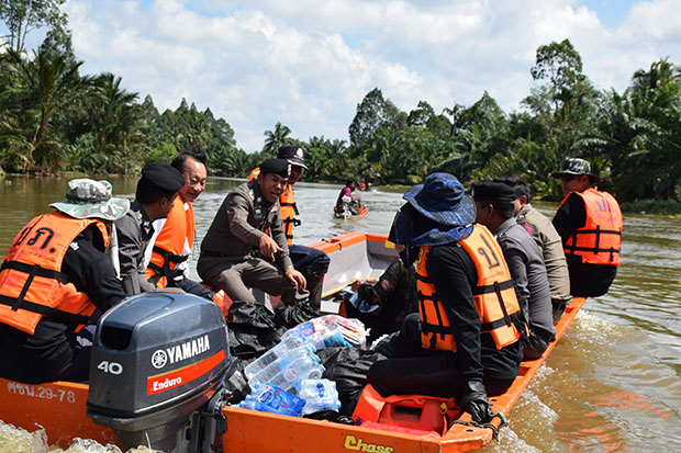 Officials use boats to distribute relief bags and clean water to help flood victims in Cha-out district in Nakhon Si Thammarat on Sunday. (Photo by Nujaree Raekrun)