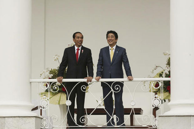 Japanese Prime Minister Shinzo Abe and Indonesian President Joko Widodo smile together during a meeting at Presidential Palace in Bogor, Indonesia, on Sunday. (AP photo)