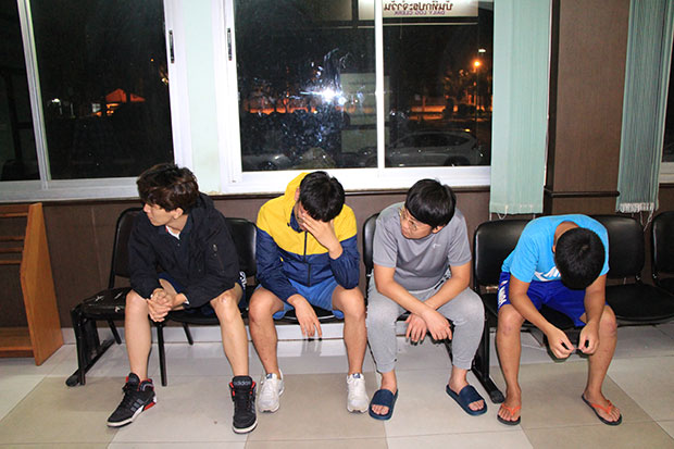 Four South Koreans wait to be processed at Bang Lamung police station after being arrested for allegedly operating online gambling in Pattaya. (Photo by Chaiyot Pupattanapong)