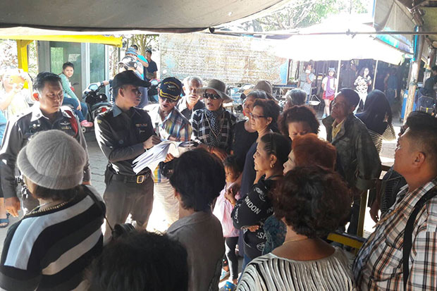 Immigration police explain the incident involving Thai tourists on Saturday to another group of Thais at the immigration checkpoint in Sangkhla Buri district of Kanchanaburi. (Photo by Piyarach Chongcharoen)