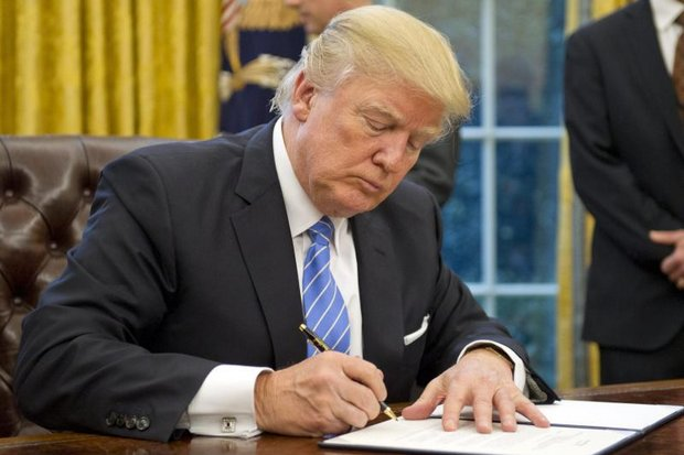 US President Donald J Trump, at the Oval Office of the White House, signs the Executive Order for the withdrawal of the United States from the Trans-Pacific Partnership (TPP). (EPA photo)