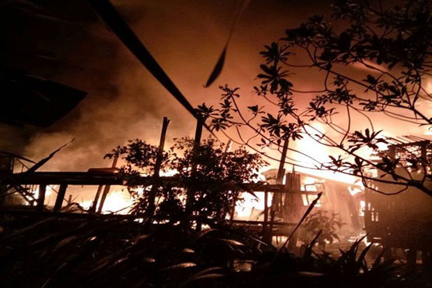 Flames engulf a Klong Toey community late Friday night, leaving many residents homeless. A total of 30 houses were destroyed in the fire, which caused no injuries. (Post Today photo)