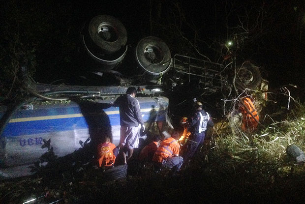 Rescue workers try to retrieve the body of the driver run over by a fuel tanker that overturned in Chaiyaphum early Saturday. (Photo by Makkawan Wannakul)