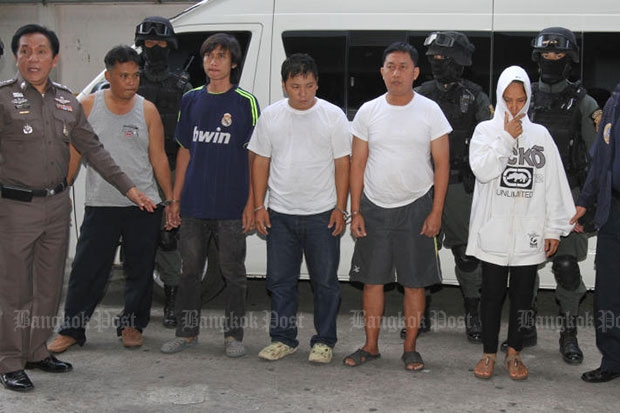 Police escort the five alleged 'men in black' to Criminal Court to request for more time to detain them during an investigation on Sept 13, 2014. (Bangkok Post file photo)