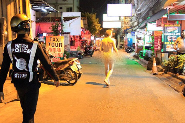 A naked foreign man, armed with a knife and a screw driver, walks along a soi in Pattaya Klang, Nong Prue in Bang Lamung district of Chon Buri, as police try to stop him. (Photo from Post Today)