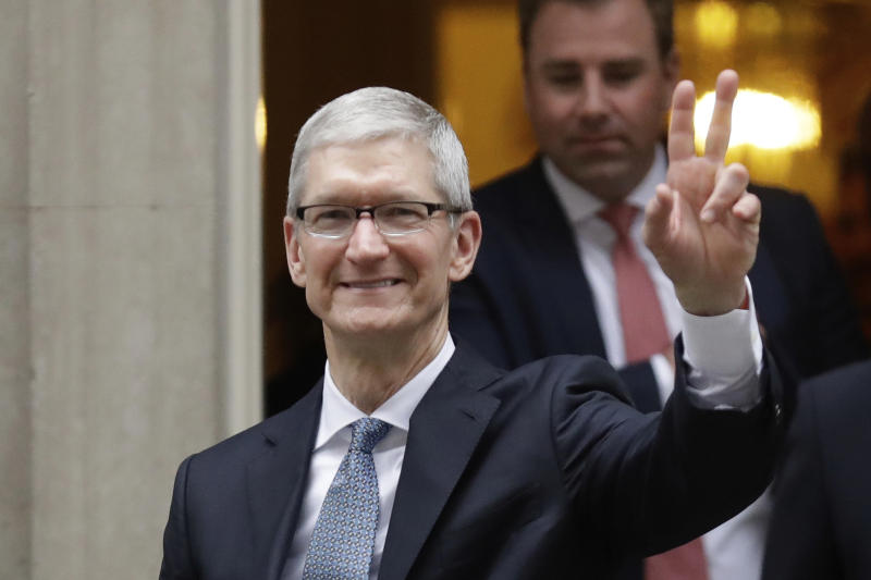 Apple chief executive officer Tim Cook waves at members of the media as he leaves 10 Downing Street in London on Thursday. (AP photo)
