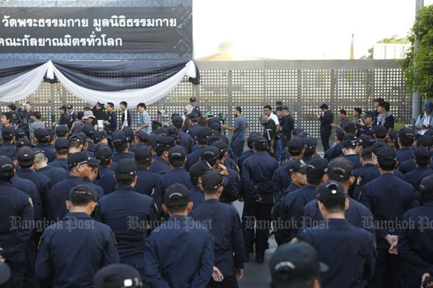 Three companies of unarmed police waited in front of the main gate of Wat Phra Dhammakaya in Khlong Luang district, Pathum Thani, on Thursday morning. (Photo by Pattarapong Chatpattarasill)
