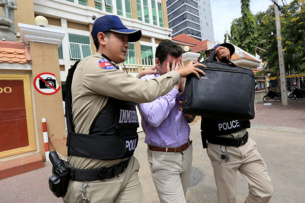 Toby James Nelham hides his face from the cameras after Cambodian immigration police arrested him in Phnom Penh on Wednesday. (Khmer Times photo)