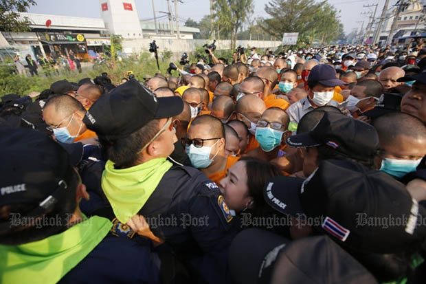 Masked monks and police tussle at the entrance to a road outside Wat Phra Dhammakaya on Monday morning. (Photo by Wichan Charoenkiatpakul)