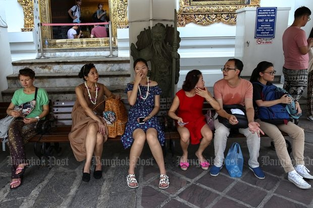 Chinese tourists take a break at Wat Pho in Bangkok on Oct 3, 2016. (Reuters photo)