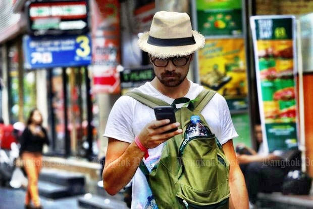 A foreign tourist looks at his mobile phone while walking along Silom Road in Bangkok. (File photo by Tanaphon Ongarttrakoon)