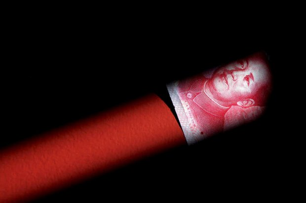 A 100-yuan note sits on the end of a firecracker. (Reuters photo)