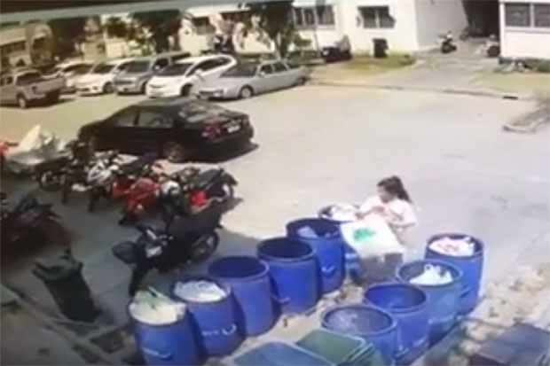 A picture grab from the video clip shows a woman dropping a bag said to contain the aborted child in a trash bin on Sunday. (Photo from father-in-law's Facebook account)