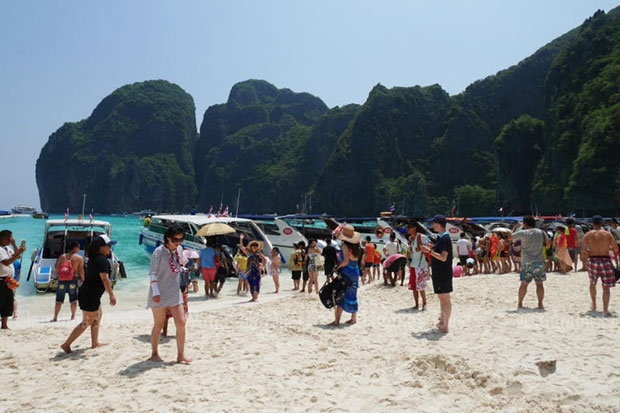 Tourists disembark from boats on the renowned Maya Bay in Phi Phi Marine National Park. (Bangkok Post file photo)