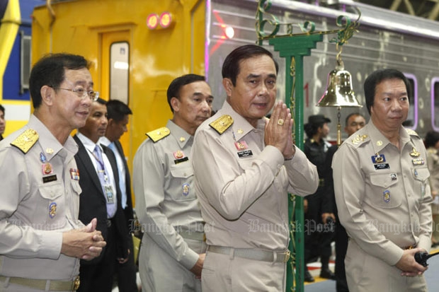 Prime Minister Prayut Chan-o-cha, centre, launches a new train at Hua Lamphong station in Bangkok last year. SRT governor Wuthichart Kalyanamitra is at right, and Transport Minister Arkhom Termpittayapaisith is at left. On Thursday the premier transferred the SRT governor to an inactive post. (Photo by Thanarak Khunton)