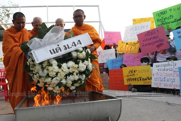 Monks stage a symbolic burning of Section 44, the provision in the interim constitution used to authorise the search of Wat Dhammakaya, in front of the Klong Luang market in Pathum Thani on Saturday. (Photo by Thiti Wannamontha)