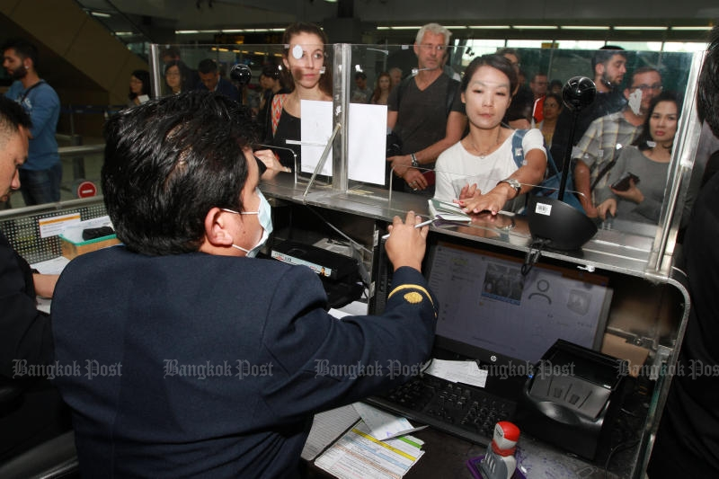 A passenger hands her passport to an immigration official at Suvarnabhumi airport on Dec 23, 2016. (Photo by Somchai Poomlard)