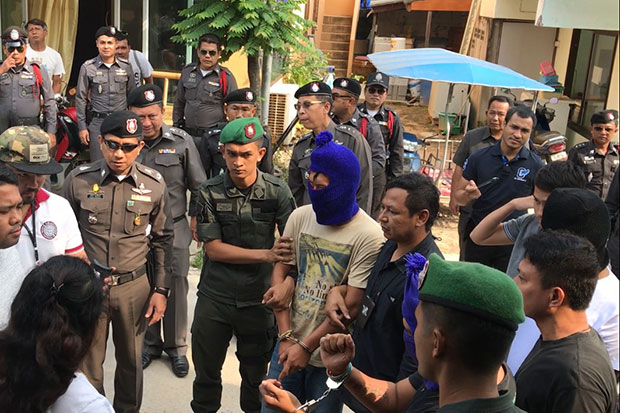 Three suspects, their faces hidden by wool hats, are taken for a crime re-enactment on Koh Phangan on Thursday. They are among five suspects, including a police officer, accused of the assault and extortion of a Russian couple. (Photo by Supapong Chaolan)