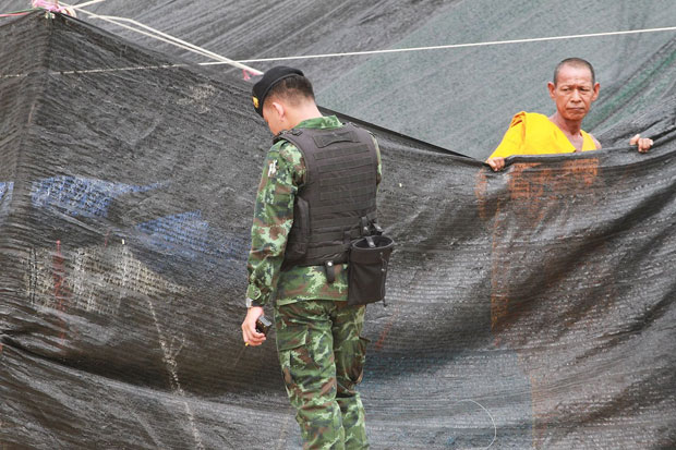 A monk keeps a wary eye on a soldier on duty at the Wat Phra Dhammakaya followers' rally site in a market just outside the temple in Khlong Luang district, Pathum Thani. (Photo by Pongpat Wongyala)