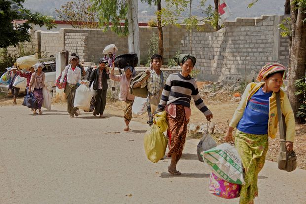 Victims of the conflict carry their belonging as they leave from the China-Myanmar border town of Laukkai, northern Shan State, Myanmar, on Tuesday. (EPA photo)