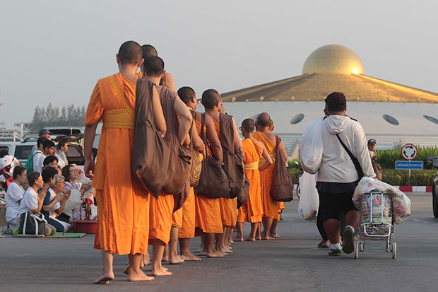Wat Phra Dhammakaya monks enter the temple on Saturday after the Department of Special Investigation decided to end the search as former abbot Phra Dhammajayo, wanted on money laundering and forest encroachment charges, could not be found. (Photo by Pongpat Wongyala)