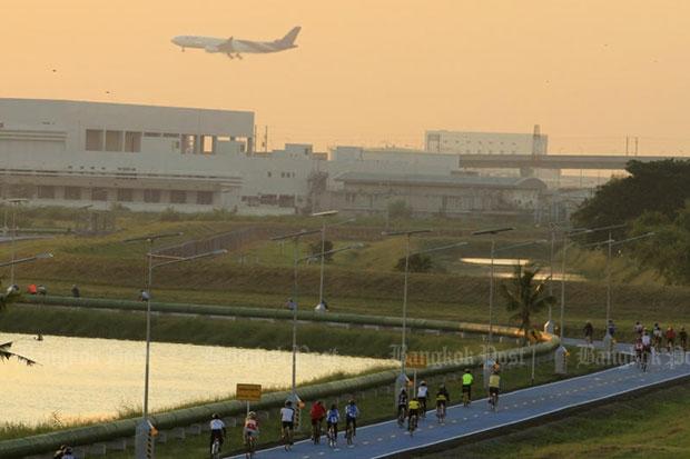 Bikers pedal in the Sky Lane as an aircraft comes into land at Suvarnabhumi airport. (Photo by Thanarak Khunton)